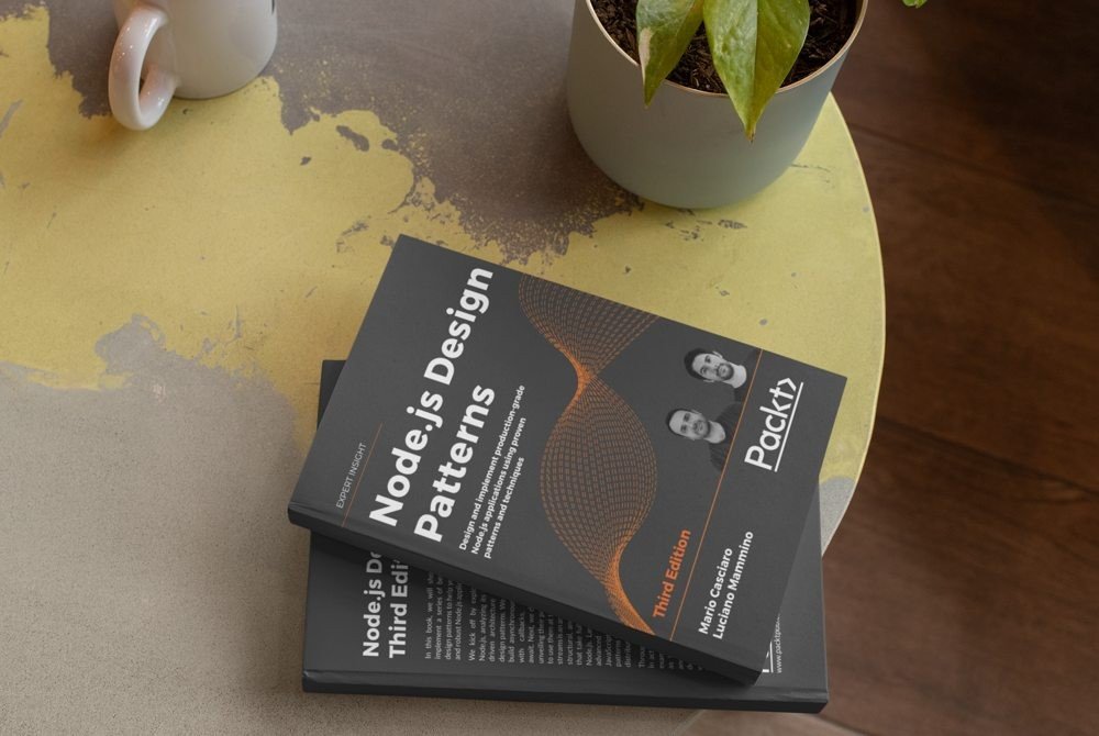 Node.js Design Patterns book on a table next to a plant